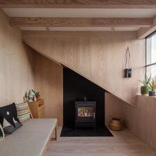 Kleines Nordisches Gästezimmer mit hellem Holzboden, Kaminofen, Kaminumrandung aus Metall, brauner Wandfarbe und beigem Boden in London