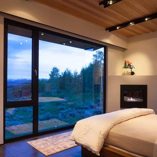 Стильный дизайн: гостевая спальня среднего размера в современном стиле с желтыми стенами, бетонным полом, угловым камином, фасадом камина из штукатурки и коричневым полом - последний тренд