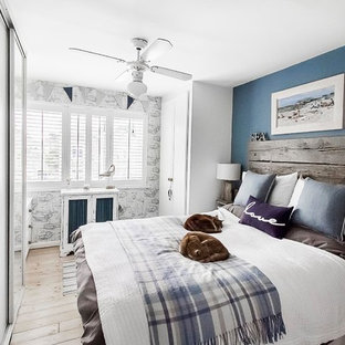 Inspiration for a medium sized beach style master bedroom in London with blue walls, light hardwood flooring, no fireplace and brown floors.