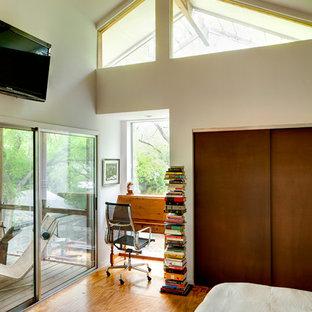 Immagine di una camera da letto contemporanea con pareti bianche e pavimento in compensato