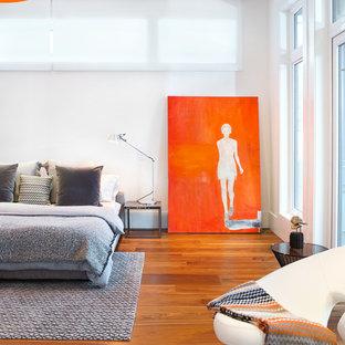 Foto di una camera da letto contemporanea con pareti bianche, pavimento in legno massello medio e pavimento arancione
