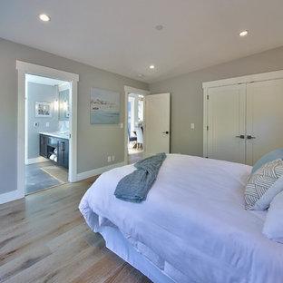 Diseño de dormitorio principal, tradicional renovado, de tamaño medio, sin chimenea, con paredes grises, suelo de madera en tonos medios y suelo marrón