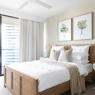 This is an example of a mid-sized beach style guest bedroom in Gold Coast - Tweed with beige walls, carpet and beige floor.