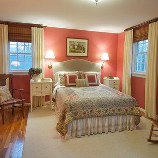 Foto di una grande camera matrimoniale tradizionale con pareti rosse, pavimento in legno massello medio e nessun camino