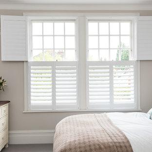 Modelo de habitación de invitados clásica, de tamaño medio, con paredes grises, moqueta, chimenea tradicional, marco de chimenea de baldosas y/o azulejos y suelo gris