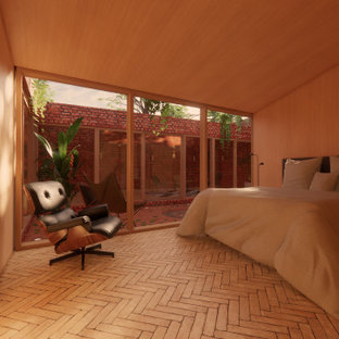 Photo of a small modern guest bedroom in Other with orange walls, brick floors, no fireplace and beige floor.