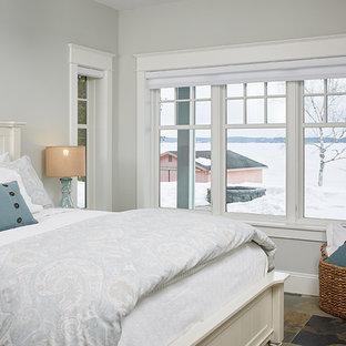 Foto de habitación de invitados costera, de tamaño medio, sin chimenea, con paredes grises y suelo de pizarra