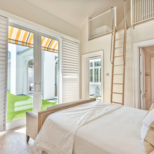 Photo of a mid-sized country loft-style bedroom in Tampa with beige walls, light hardwood floors and no fireplace.