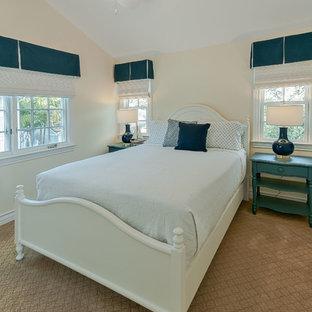Imagen de habitación de invitados costera, de tamaño medio, sin chimenea, con paredes amarillas y moqueta