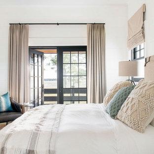 Großes Landhausstil Hauptschlafzimmer mit weißer Wandfarbe, hellem Holzboden, braunem Boden und Holzwänden in Charleston