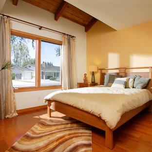 サクラメントの中サイズのコンテンポラリースタイルのおしゃれな客用寝室 (黄色い壁、無垢フローリング、暖炉なし)