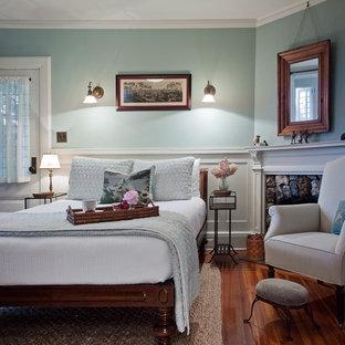 Imagen de habitación de invitados de estilo de casa de campo con paredes azules, suelo de madera en tonos medios y chimenea de esquina