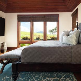 Esempio di una camera degli ospiti tropicale di medie dimensioni con pareti bianche, pavimento in legno massello medio, pavimento marrone e nessun camino