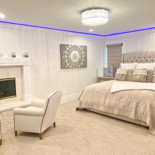 Exemple d'une grand chambre tendance avec un mur blanc, une cheminée standard, un manteau de cheminée en pierre de parement, un sol beige et un plafond décaissé.