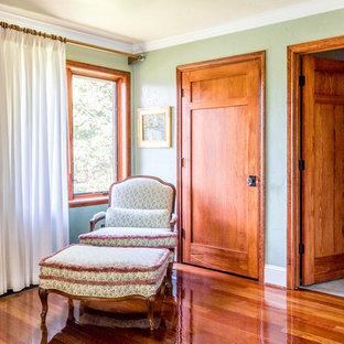 Imagen de habitación de invitados clásica, de tamaño medio, sin chimenea, con paredes verdes, suelo de madera en tonos medios y suelo rojo