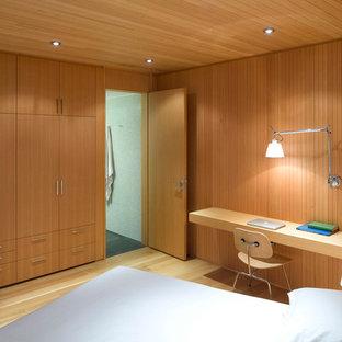 Diseño de dormitorio principal, escandinavo, grande, sin chimenea, con suelo de madera clara, paredes marrones y suelo marrón