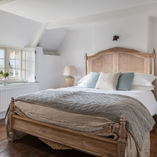 This is an example of a romantic bedroom in Cornwall with white walls, dark hardwood flooring and brown floors.