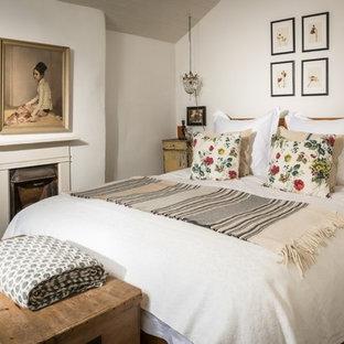 Foto de dormitorio principal, de estilo de casa de campo, de tamaño medio, con paredes blancas, moqueta, chimenea tradicional, marco de chimenea de yeso y suelo beige