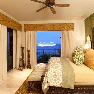 На фото: большая хозяйская спальня в средиземноморском стиле с бежевыми стенами и полом из травертина без камина