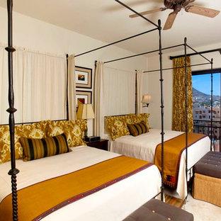 На фото: с высоким бюджетом большие гостевые спальни в средиземноморском стиле с бежевыми стенами и полом из травертина без камина