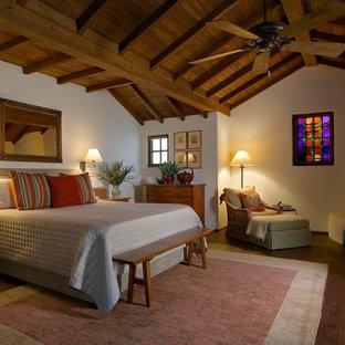 Mittelgroßes Mediterranes Hauptschlafzimmer mit weißer Wandfarbe, braunem Holzboden, Eckkamin und verputzter Kaminumrandung in Santa Barbara