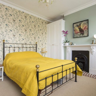Inspiration for a classic bedroom in London with green walls, carpet, a standard fireplace and beige floors.