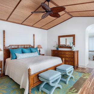 Modelo de dormitorio principal, exótico, grande, con paredes blancas y suelo de bambú