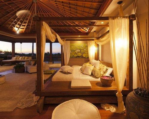 large island style master medium tone wood floor bedroom photo in hawaii with beige walls