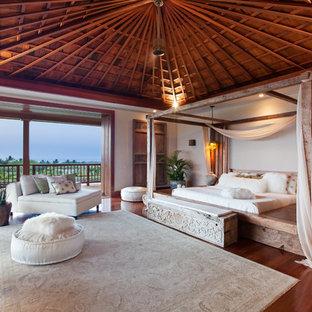 Réalisation d'une très grande chambre parentale ethnique avec un sol en bois brun et un mur blanc.