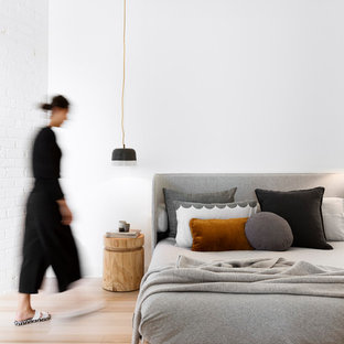 Inspiration for a scandinavian bedroom in Melbourne with white walls, light hardwood floors and no fireplace.