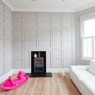 Large elegant medium tone wood floor bedroom photo in London with gray walls and a wood stove
