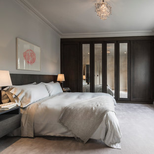 Mid-sized transitional guest bedroom in London with carpet, white walls and no fireplace.