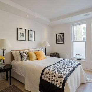 Design ideas for a medium sized classic bedroom in London with white walls and light hardwood flooring.