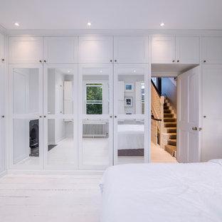 ロンドンのトランジショナルスタイルのおしゃれな主寝室 (白い壁、塗装フローリング、標準型暖炉、木材の暖炉まわり、白い床) のレイアウト