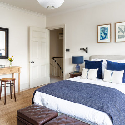 Example of a transitional bedroom design in London with white walls