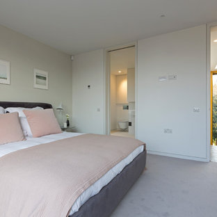 Photo of a medium sized contemporary grey and pink bedroom in London with white walls, carpet, grey floors and a feature wall.