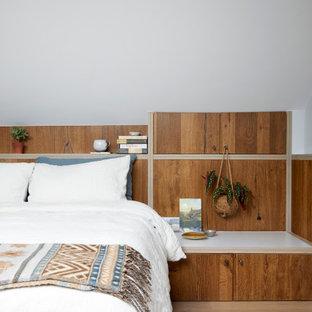 Imagen de dormitorio tipo loft, rústico, pequeño, con paredes azules y suelo de madera en tonos medios