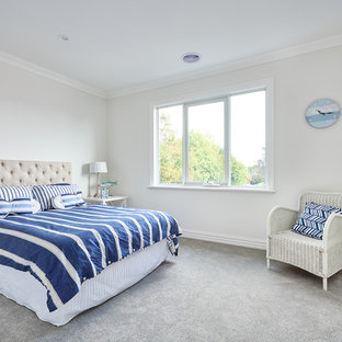 Inspiration for a beach style bedroom in Melbourne with beige walls, carpet and grey floor.