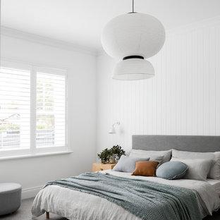 メルボルンのコンテンポラリースタイルのおしゃれな主寝室 (白い壁、カーペット敷き、標準型暖炉、木材の暖炉まわり、グレーの床) のインテリア