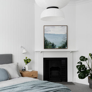 Inspiration for a contemporary master bedroom in Melbourne with white walls, carpet, a standard fireplace, a wood fireplace surround and grey floor.