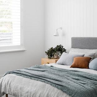 Ejemplo de dormitorio principal, contemporáneo, con paredes blancas, moqueta, chimenea tradicional, marco de chimenea de madera y suelo gris
