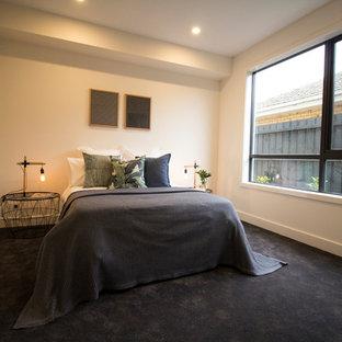 Ejemplo de habitación de invitados actual, grande, con paredes blancas, moqueta y suelo azul