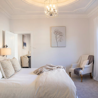 Photo of a beach style master bedroom in Newcastle - Maitland with white walls, carpet and beige floor.
