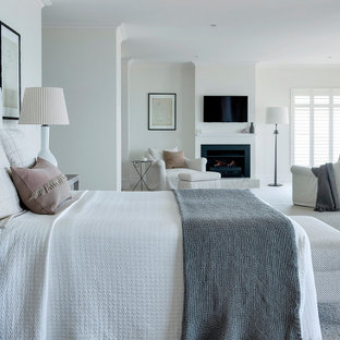 This is an example of a beach style bedroom in Other with white walls, carpet, a standard fireplace and grey floor.