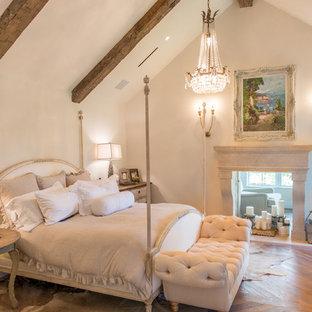 Foto de dormitorio principal, tradicional, grande, con paredes blancas, suelo de madera en tonos medios, chimenea de doble cara, marco de chimenea de piedra y suelo marrón