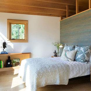 Retro inredning av ett huvudsovrum, med vita väggar, ljust trägolv och beiget golv