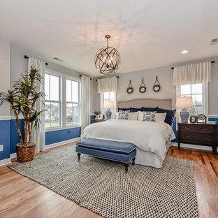 Imagen de dormitorio principal, campestre, de tamaño medio, sin chimenea, con paredes azules y suelo de madera clara