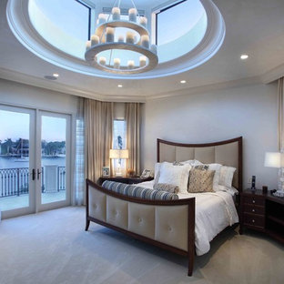 Huge tuscan master carpeted and gray floor bedroom photo in Miami with beige walls