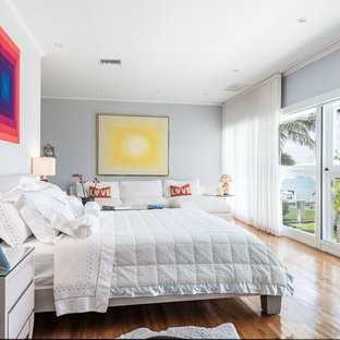Inspiration for a contemporary medium tone wood floor bedroom remodel in Miami with gray walls