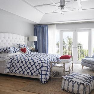 Coastal medium tone wood floor bedroom photo in Miami with gray walls